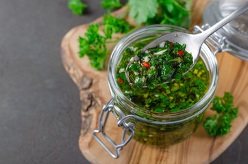 Spoed Foto op Canvas Kruiderij Traditional argentinian chimichurri sauce made of parsley, cilantro, garlic and chili pepper in a glass jar, focus on a spoon with sauce. Selective focus, horizontal image