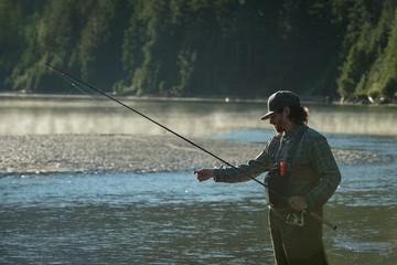 Man adjusting reel while fishing in river