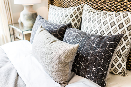 Closeup of new bed comforter with decorative pillows, headboard in bedroom in staging model home, house or apartment