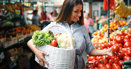 Portrait of beautiful woman holding shopping basket Wall mural