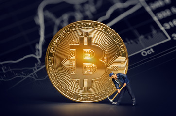 miner figurine with pickaxe and shiny bitcoin in front of bitcoin trading market data chart. virtual cryptocurrency concept