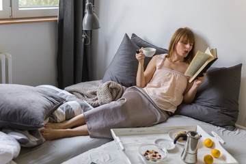 Books and coffee are a great start to the day - women reading book and drink coffee in bed