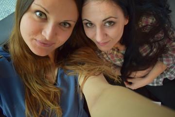 two smiling friends take selfies, two white girls