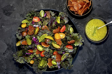 Fried Provolone Kale Salad with Dill Pesto vinaigrette served with wine. Photographed on a black/grey background.
