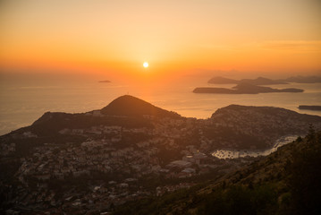Sunset on the Adriatic sea with layers mountains on the horizon. Beautiful panoramic view of Dubrovnik, Croatia.
