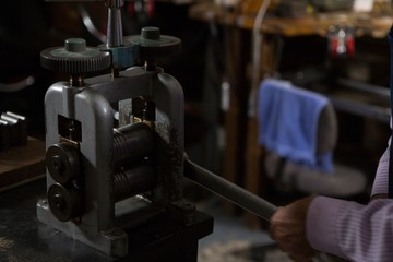 Goldsmith working on machine in workshop