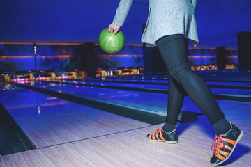 A woman in black clothes plays a bowling red with a bright layer. Active leisure for a bowling game