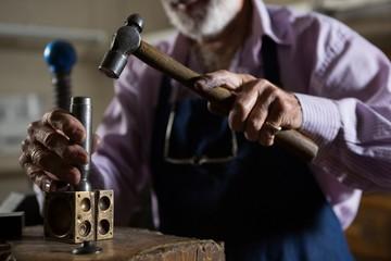 Goldsmith using hammer in workshop