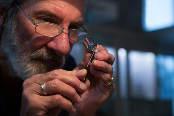 Goldsmith using magnifying glass in workshop