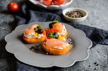Sweet potato slices topped with cream cheese, smoked salmon, olives and corn