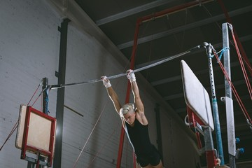 Male gymnast practicing gymnastics on the horizontal bar