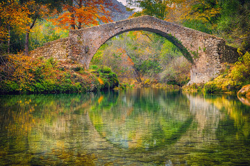 Ancient roman stone bridge Pont des Tuves across the Siagne river surrounded by yellow autumn trees near Saint-Cezaire-sur-Siagne, Alpes Maritimes, France