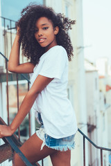 Young beautiful black woman on the stairs posing