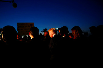 U.S. President Donald Trump shakes hands with people after disembarking from Air Force One in West Palm Beach, Florida