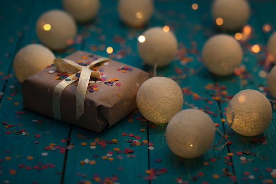 Gift box and Christmas and New Year cotton light balls string on wooden table in the night