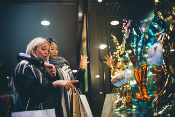 Blonde woman and asian woman go shopping.