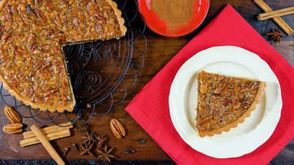 American style pecan pie on rustic dark wood table overhead for Thanskgiving or Christmas celebrations