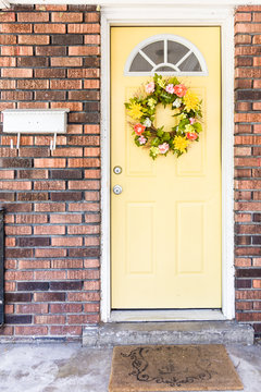Bold yellow accent front door of old brick house, colorful floral wreath