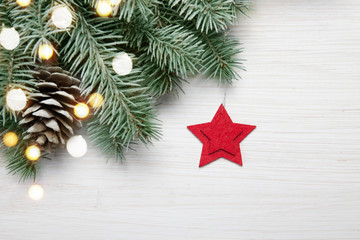 Christmas background. Fir tree on white wooden background with lights and red star