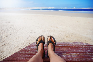 Woman laying on the beach. Feet close up.