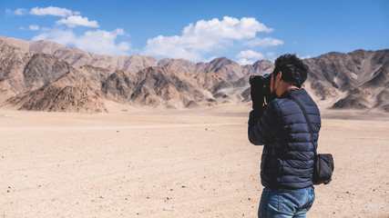 A man photographer taking a landscape photo of desert , mountains and blue sky