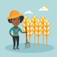 Young african-american farmer standing with a pitchfork on the background of a wheat field. Smiling farmer working with a pitchfork in a wheat field. Vector cartoon illustration. Square layout.