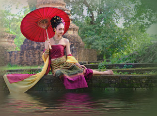 Asian woman wearing typical dress with red umbrella,Thai costume.