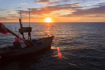 Fishing boat in the sea at sunset.
