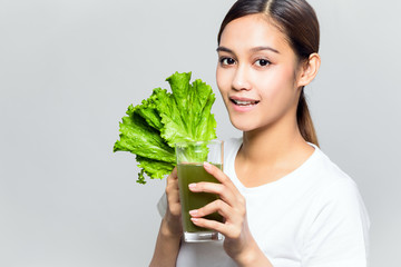 Young woman drinking a glass of vegetable juice.