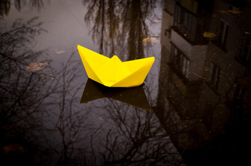 Yellow paper boat and a gloomy autumn city. Hope for success