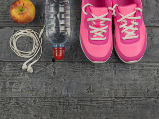 Beautiful pink sneakers, headphones, water and apples on a wooden floor. View from above.