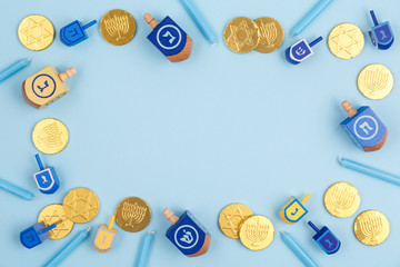 Blue background with multicolor dreidels, menora candles and chocolate coins. Hanukkah and judaic holiday concept.