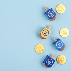 Blue background with multicolor dreidels and chocolate coins. Hanukkah and judaic holiday concept.