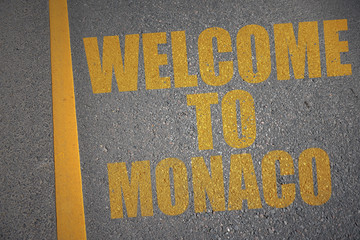 asphalt road with text welcome to monaco near yellow line.