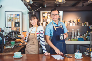 Young Asian barista standing with smile in their coffee shop