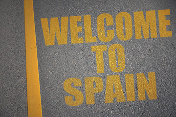 asphalt road with text welcome to spain near yellow line.