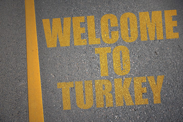 asphalt road with text welcome to turkey near yellow line.