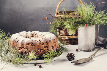Traditional homemade christmas cake with nuts and dried fruit on light grey background. Christmas decoration. Selective focus. Vintage tone style