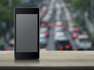 Modern smart phone with blank grey screen on wooden table over blur of rush hour with cars and road