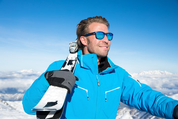 Young, sexy man is skiing in winter paradise in the alps with a beautiful blue sky and wonderful white snowy mountains
