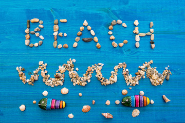 Word beach written with beach stones as a sign, showing direction on blue wooden background