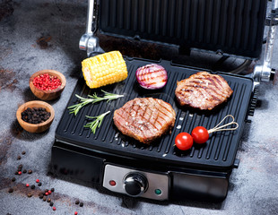 Fototapete - Beef steak with vegetables. Preparation on electric grill