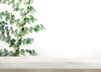 Wood table top on white wall with leaf background.