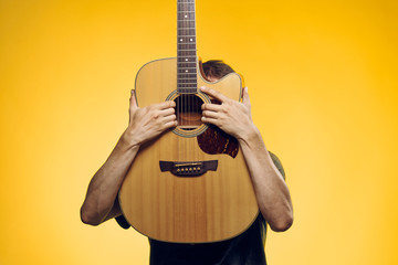 Man on a yellow background holds a guitar, musical instruments