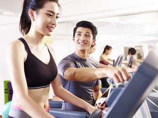 young asian adults exercising on treadmill helped by male trainer