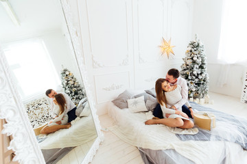 Happy couple have fun in the room with a large mirror and Christmas tree