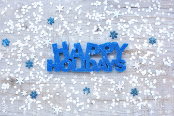 "Greeting ""Happy Holidays"", snowflakes and confetti on a light wooden background. Top view."