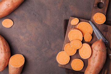 Raw sweet potato whole and chopped on kitchen table top view. Copy space for text.
