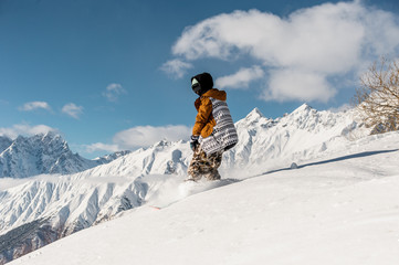 Female snowboarder in sportswear riding on the mountain slope