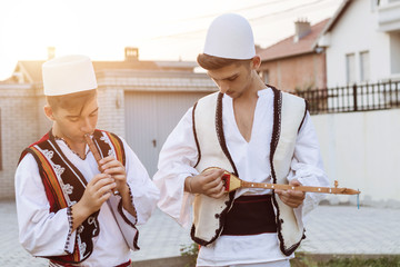 teen boys in traditional albanian costume playing music with flute and string instrument in the evening sunlight Wall mural